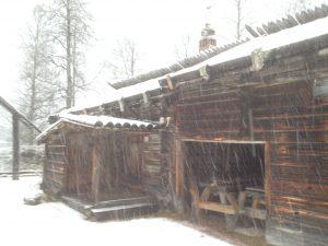 Ryggstuga från Bogg-gården i Väsa by. Stugan har friliggande takåsar utan innertak. Det finns även ett torrdass vid ingången.
