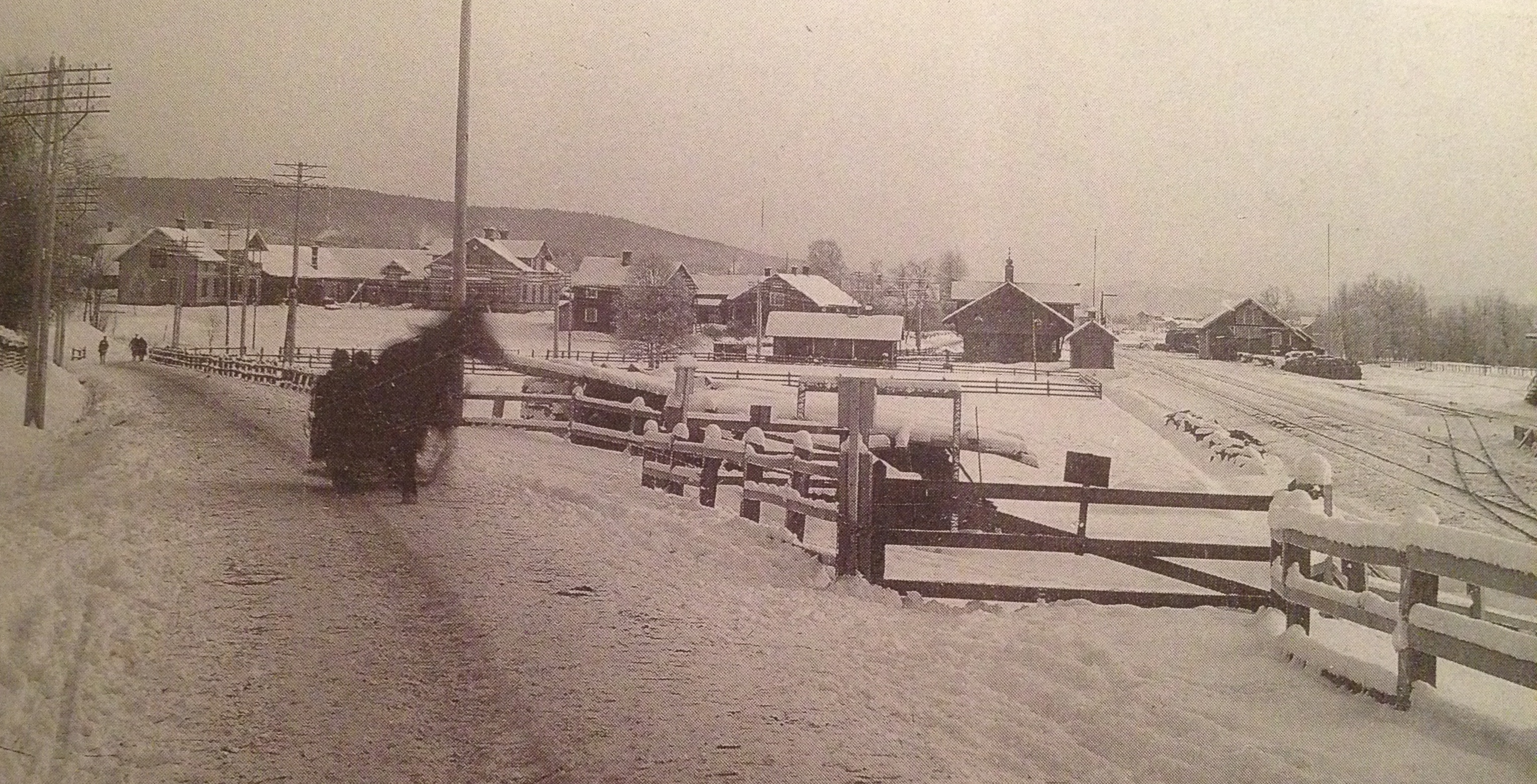 """""""Vy söderut mot Lassisgården och järnvägsstationen; t.h. kolbryggan (bortom lokstallet) där kolkörarna tömde sina kolryssar för vidare befordran. Foto C. Ehrner omkr. 1905."""" Bilden hämtad ur """"Älvdalens kyrkby när seklet var ungt"""" av Helge Lindberg"""
